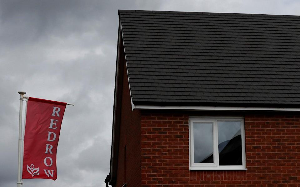 The company logo of construction company Redrow is pictured on a flag at a new housing development near Manchester northern England - Phil Noble/Reuters