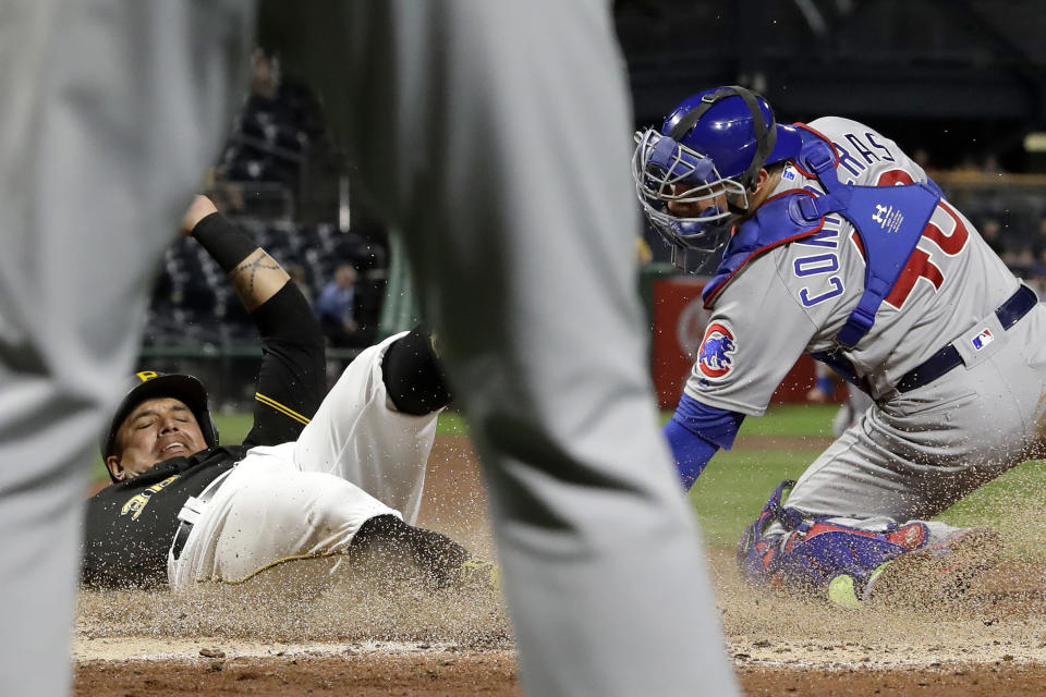 Pittsburgh Pirates' Jose Osuna, left, is framed by the legs of Chicago Cubs starting pitcher Jon Lester, as he scores past the attempted tag by catcher Willson Contreras on a double by Erik Gonzalez during the fourth inning of a baseball game in Pittsburgh, Wednesday, Sept. 25, 2019. (AP Photo/Gene J. Puskar)