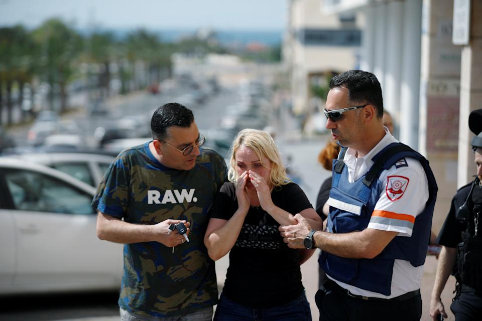 A woman in Ashkelon at the scene of a rocket attackReuters