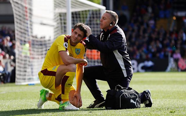 <span>James Tarkowski receives treatment after the Burnley defender was hit by a missile thrown from the stands at Selhurst Park </span> <span>Credit:  REUTERS </span>