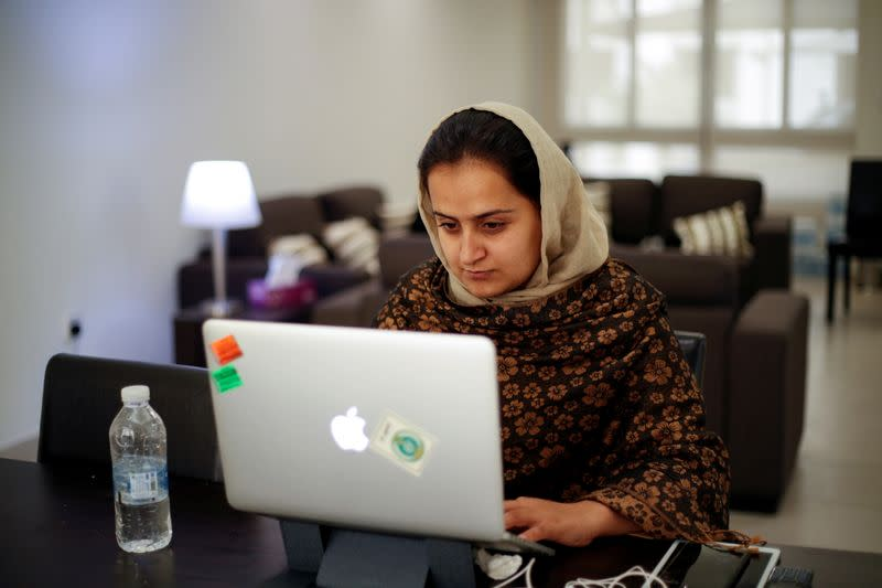 Afghan news anchor Beheshta Arghand works on laptop at a temporary residence compound in Doha