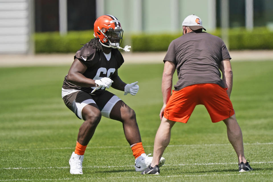 Cleveland Browns tackle James Hudson III, left, runs a drill during an NFL football rookie minicamp at the team's training camp facility, Friday, May 14, 2021, in Berea, Ohio. (AP Photo/Tony Dejak)
