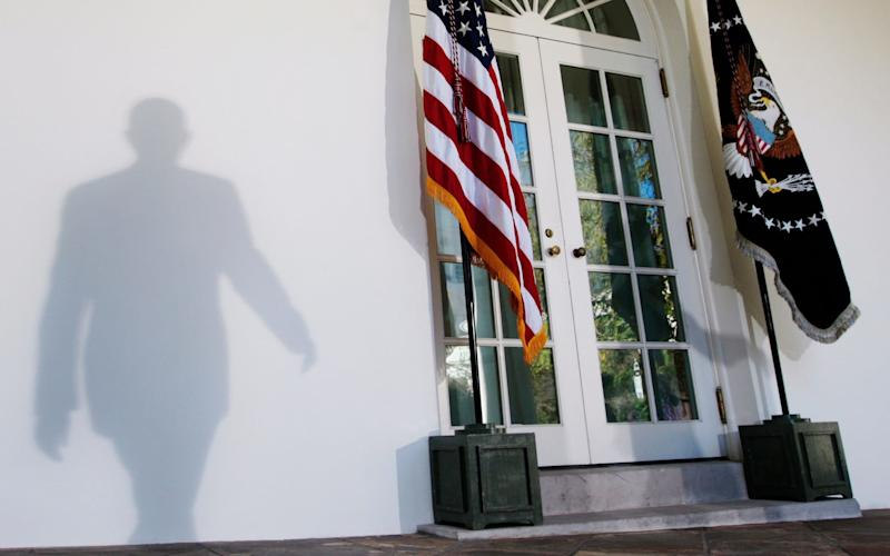 President Barack Obama casts a shadow on the wall at the White House  - AP