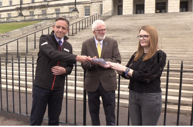 Travel agent Damien Murphy hands a letter to Caoimhe Archibald, chairwoman of Stormont's Economy Committee
