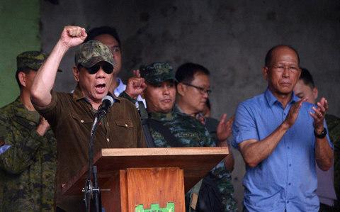 "Philippines President Rodrigo Duterte raises a clenched fist, as he shouts declaring Marawi ""liberated"" during a ceremony inside the battle area of Bangolo district in Marawi on October 17, 2017 - Credit: AFP"