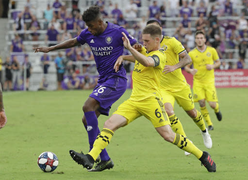 Columbus Crew's Will Trapp (6) clears the ball from Orlando City's Carlos Ascues, left, during the first half of an MLS soccer match Saturday, July 13, 2019, in Orlando, Fla. (AP Photo/John Raoux)
