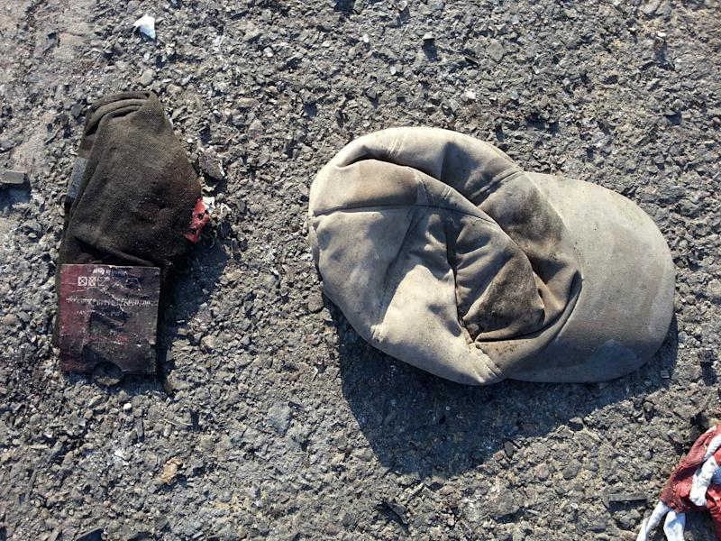 A cap and a pair of new socks are seen on the ground after a suicide car bomb attack on the road between the border town of Rafah and the coastal city of el-Arish, Egypt, Wednesday, Nov. 20, 2013. A suicide bomber rammed his explosive-laden car into one of two buses carrying off-duty soldiers in Egypt's turbulent region of northern Sinai on Wednesday, killing nearly a dozen and wounding dozens more and wounding dozens more, security and military officials said. (AP Photo)