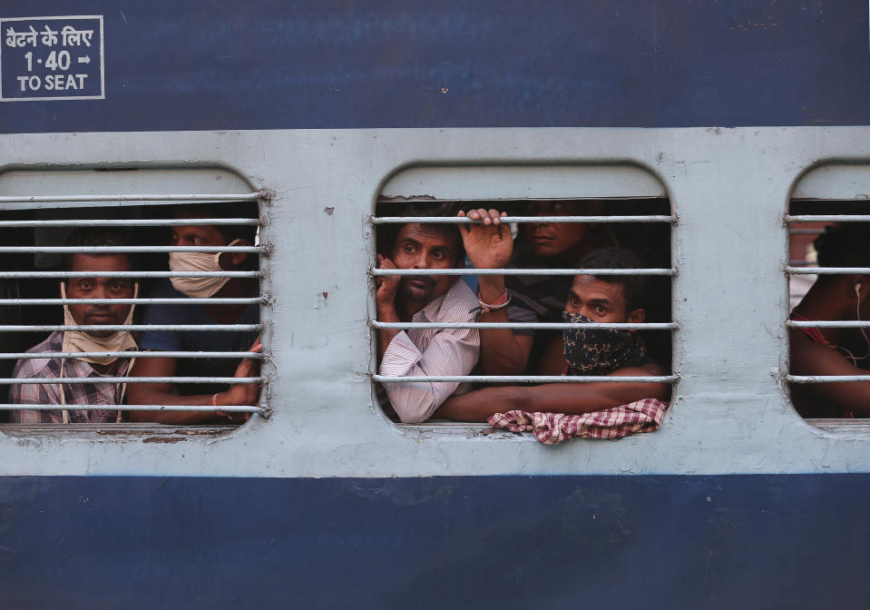 Migrant workers look out a train window before moving to their home states, at Hyderabad Railway Station in Hyderabad, India, Saturday, May 23, 2020. India's lockdown was imposed on March 25 and has been extended several times. On May 4, India eased lockdown rules and allowed migrant workers to travel back to their homes, a decision that has resulted in millions of people being on the move for the last two weeks. (AP Photo/Mahesh Kumar A.)