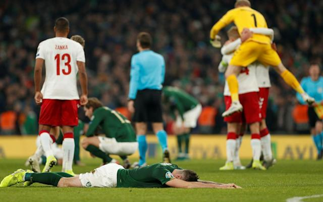 Ireland's players collapse to the turf as Denmark celebrate - Action Images via Reuters