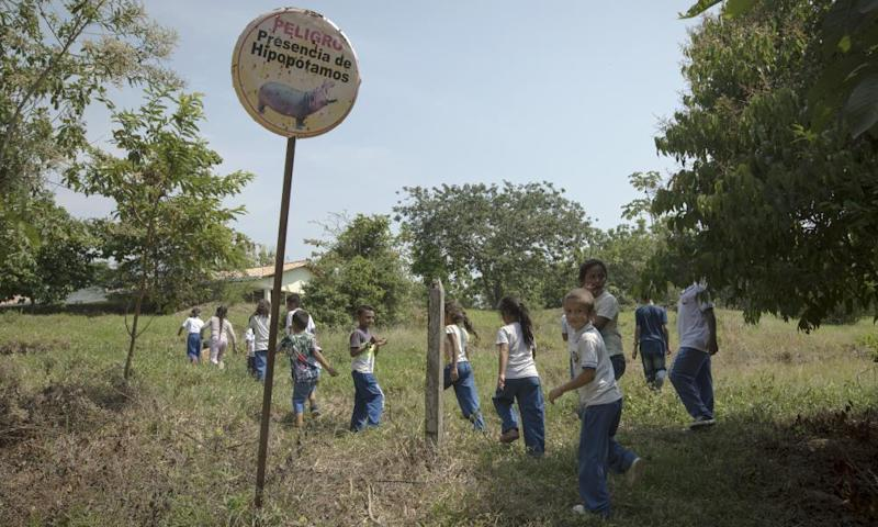 Children walk past a sign warning of the danger of hippos near the Hacienda Nápoles.
