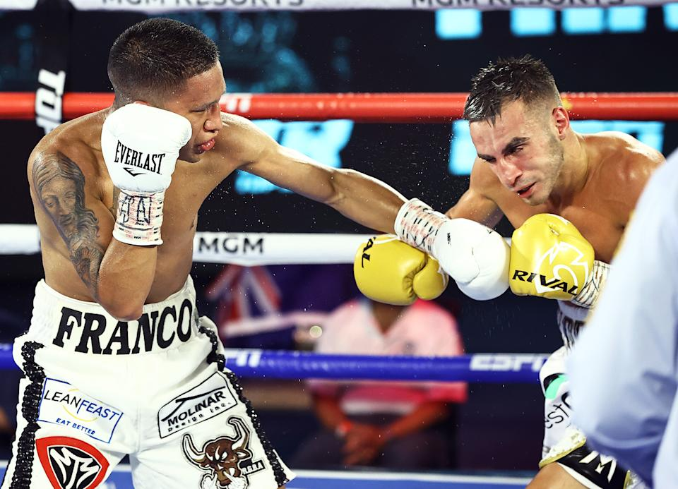 Joshua Franco (L) lands a left hands to Andrew Moloney en route to lifting the WBA super flyweight title via a unanimous decision Tuesday in Las Vegas. Judges scored it 114-113 twice and 115-112. (Mikey Williams/Top Rank)