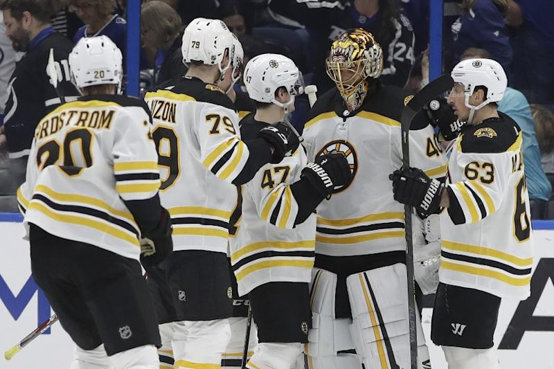 Boston Bruins goaltender Tuukka Rask (40) celebrates with teammates, left wing Brad Marchand (63), defenseman Torey Krug (47), defenseman Jeremy Lauzon (79), and center Joakim Nordstrom (20) after defeating the Tampa Bay Lightning during an NHL hockey game Tuesday, March 3, 2020, in Tampa, Fla. (AP Photo/Chris O'Meara)