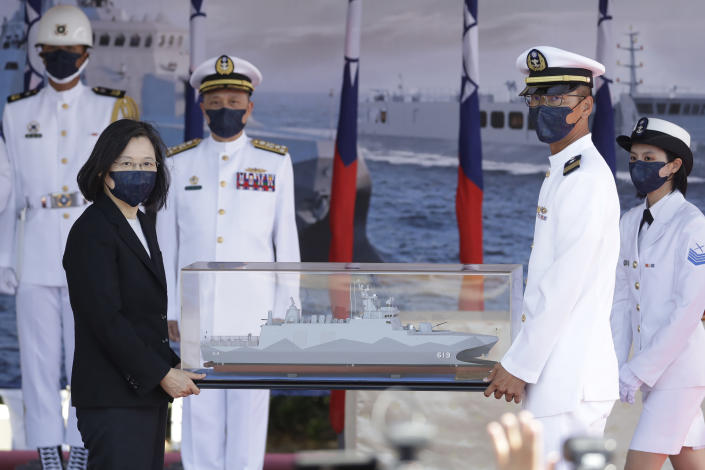 Taiwan's President Tsai Ing-wen, left, holds a model ship during the commissioning ceremony of the the domestically made Ta Jiang warship at the Suao naval base in Yilan county, Taiwan, Thursday, Sept. 9, 2021. Taiwan's president oversaw the commissioning of a new domestically made navy warship Thursday as part of the island's plan to boost indigenous defense capacity amid heightened tensions with China. (AP Photo/Chiang Ying-ying)