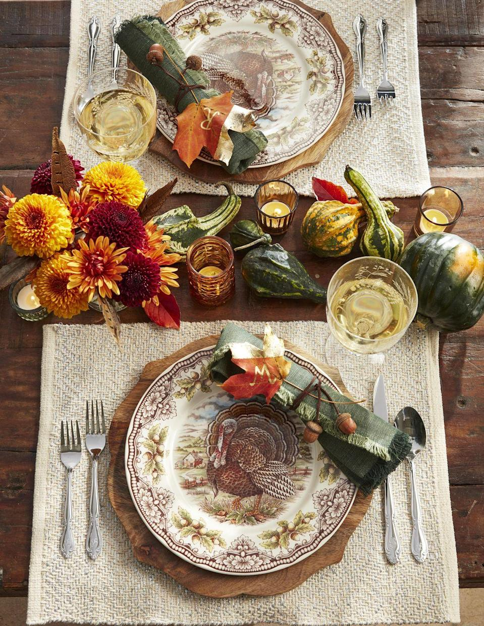 <p>Nature is the theme of this classically fall hued table. <strong><br></strong></p><p><strong>Make the crafts</strong>: Hot glue acorns to lengths of brown waxed twine and use to tie up rolled napkins. Apply gold leaf to a portion of a preserved maple leaf and use a gold paint pen to mark with guest's initials. </p>