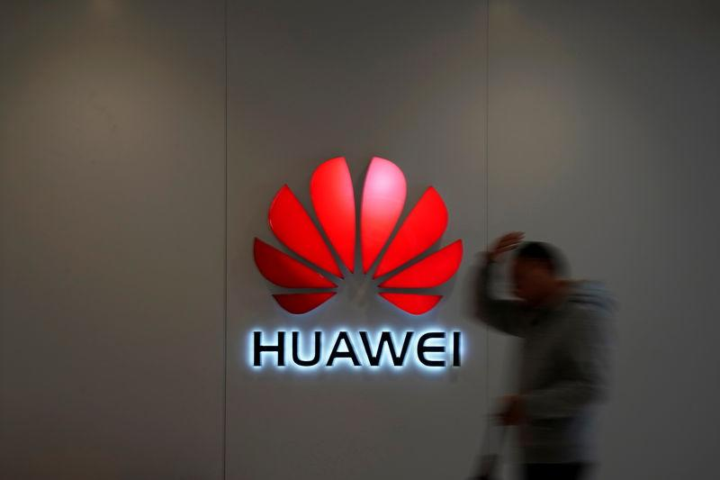 Man walks by a Huawei logo at a shopping mall in Shanghai
