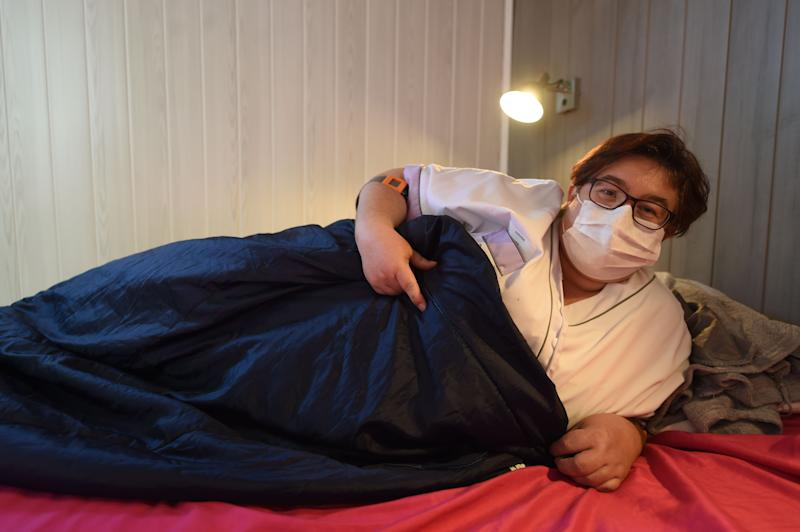 Sandrine Lalouze, 42 years old caregiver, mother of two daughters aged 12 and 16, smiles behind her protective mask as she poses in a bedroom of a dorm-truck, normally used to host participants of Le Mans Classic race, installed in front of the retirement home, in Bouere, western France, on April 14, 2020, on the 29th day of a strict lockdown aimed at curbing the spread of the COVID-19 pandemic, caused by the novel coronavirus. - The staff sleep in the dorm-truck next to the retirement home in order to protect the 60 residents from possible contamination while protecting their families. (Photo by JEAN-FRANCOIS MONIER / AFP) (Photo by JEAN-FRANCOIS MONIER/AFP via Getty Images)