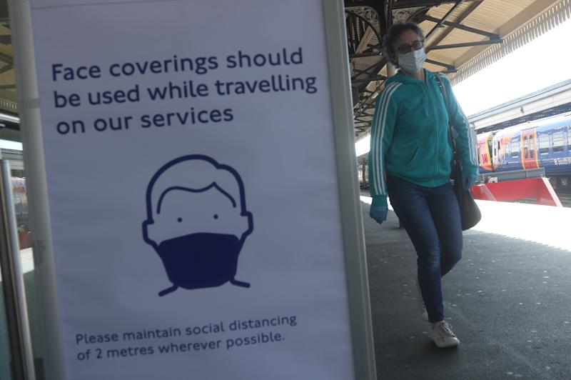 A sign advising passengers to wear a face mask at Clapham Junction station, London, as train services increase as part of the easing of coronavirus lockdown restrictions. (Photo by Yui Mok/PA Images via Getty Images)