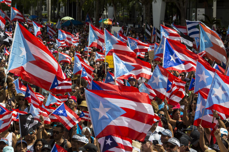People march with Puerto Rican national flags to celebrate the resignation of Gov. Ricardo Rossello who announced overnight that he is resigning Aug. 2 after weeks of protests over leaked obscene, misogynistic online chats, in San Juan, Puerto Rico, Thursday, July 25, 2019. (AP Photo/Dennis M. Rivera Pichardo)