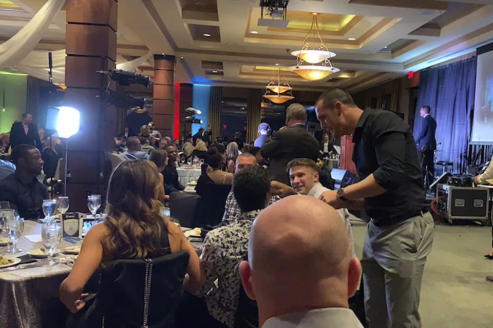 In this still image taken from video, Las Vegas Raiders quarterback Derek Carr, right, meets with people at a charity event held by teammate Darren Waller on Monday, Sept. 28, 2020, in Henderson, Nev. Several Las Vegas Raiders players attended a charity event held by teammate Darren Waller that might have violated league rules for the coronavirus pandemic. The Darren Waller Foundation held a fundraising event at a country club just outside Las Vegas to help young people overcome drug and alcohol addiction. Players were seen on video without masks during the indoor event while talking and mingling with guests, who also weren't wearing masks. (Cassie Soto/Las Vegas Review-Journal via AP)