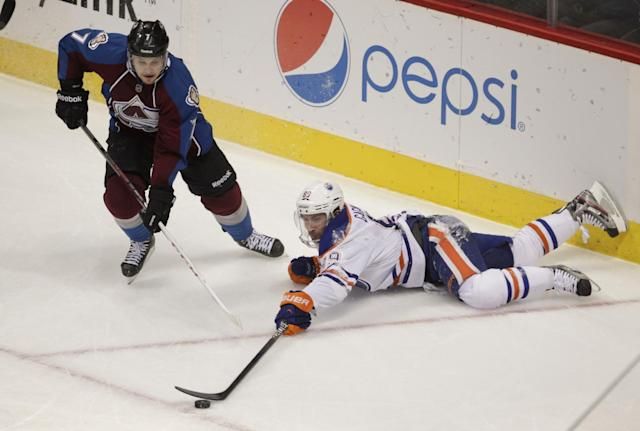 Edmonton Oilers center Sam Gagner (89) reaches for the puck against Colorado Avalanche center John Mitchell (7) during the first period of an NHL hockey game in Denver, Thursday, Dec. 19, 2013. (AP Photo/Joe Mahoney)