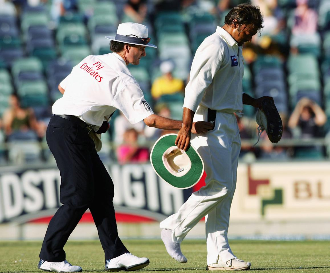 PERTH, AUSTRALIA - DECEMBER 17:  Shoaib Akhtar of Pakistan leaves the field with an injured leg as umpire Brent Bowden puts something in his pocket during day two of the First Test between Australia and Pakistan played at the WACA on December 17, 2004 in Perth, Australia.  (Photo by Hamish Blair/Getty Images)