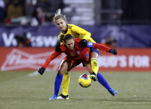 Sweden defender Nathalie Bjorn, top, tries to pass the ball against United States forward Carli Lloyd during the second half of a women's international friendly soccer match in Columbus, Ohio, Thursday, Nov. 7, 2019. (AP Photo/Paul Vernon)