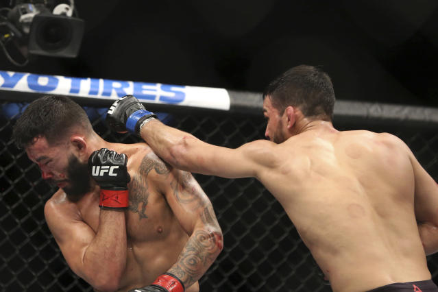 Julio Arce, right, hits Dan Ige during a mixed martial arts bout at UFC 220, Saturday, Jan. 20, 2018, in Boston. Arce won via decision. (AP Photo/Gregory Payan)