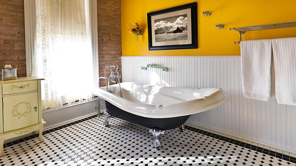 A modern contemporary classic bathroom design, furnished with a classic painted cabinet, sepia toned picture on the wall, exposed brick wall and a window, a claw foot bath tub and black and white tile pattern on the floor.
