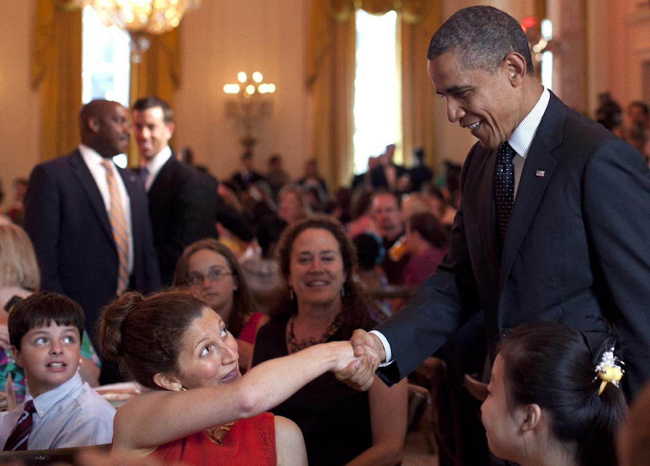 """President Barack Obama shakes hands during the Kids' """"State Dinner,"""" hosted by first lady Michelle Obama, Monday, Aug. 20, 2012, in the East Room of the White House in Washington (AP Photo/Carolyn Kaster)"""