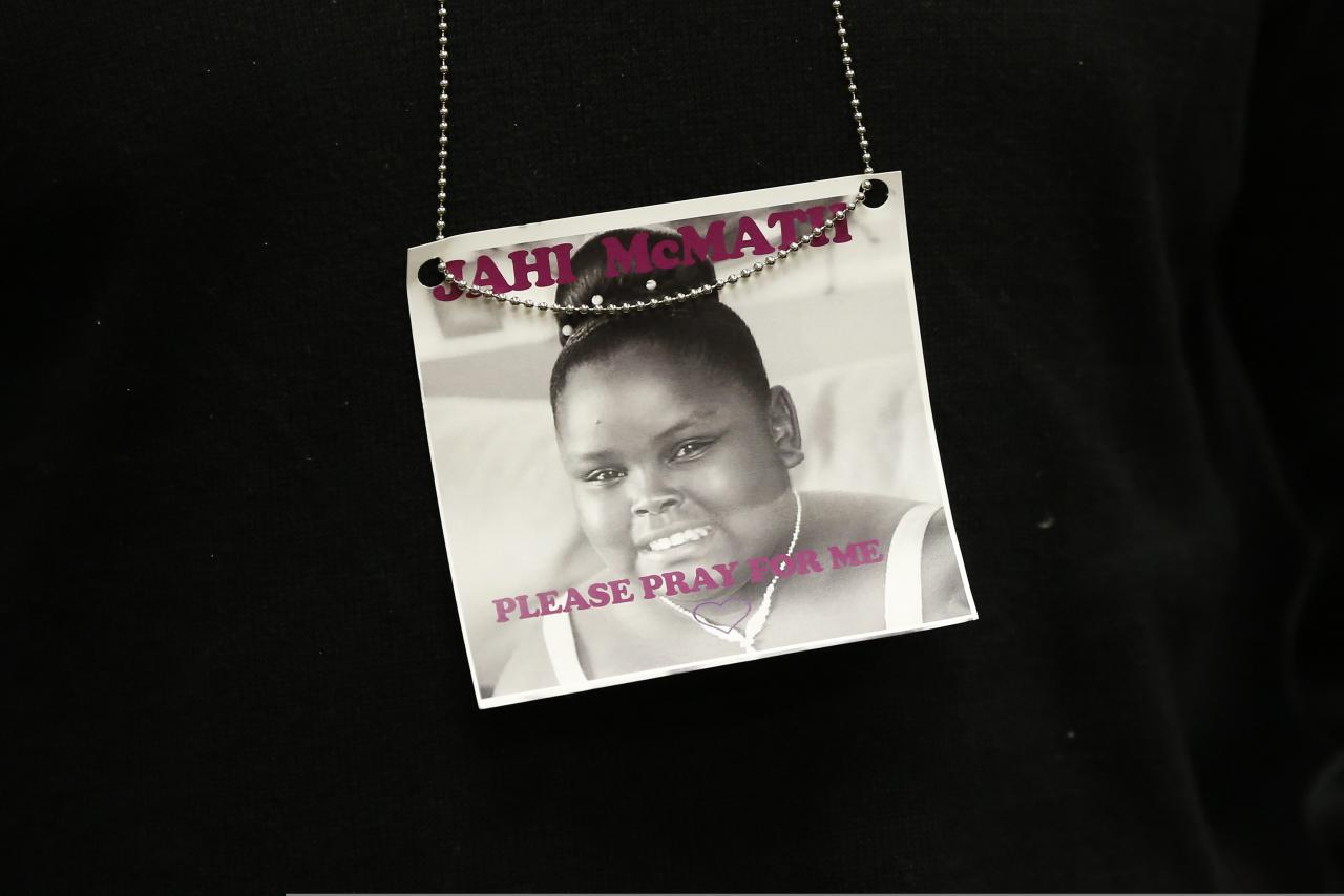 A photograph of 13-year-old Jahi McMath is seen on a necklace in Oakland, California in this December 24, 2013 file photo. Relatives of the girl declared brain dead after complications from a tonsillectomy want her moved to a long-term care facility, but face resistance from the hospital where she is due to be disconnected from a breathing machine on Monday.REUTERS/Stephen Lam/Files (UNITED STATES - Tags: HEALTH CRIME LAW)