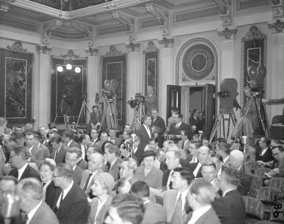 FILE - In this Jan. 19, 1955, file photo photographers have their equipment set up at the back of the room as reporters take their places for President Dwight Eisenhower's news conference in Washington. It was the first conference at which full picture coverage was permitted. Photographer with three cameras at center is John Rooney of The Associated Press. Just below Rooney, Marvin Arrowsmith, AP reporter, enters the room carrying a note board under his arm. (AP Photo/Bill Allen, File)