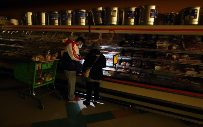 FILE - Customers use the light from a cell phone to look in the meat section of a grocery store Tuesday, Feb. 16, 2021, in Dallas. Even though the store lost power, it was open for cash only sales. A series of winter storms and widespread power outages gripping Texas and other states not used to such extreme low temperatures are creating big challenges in the nation's food supply networks.(AP Photo/LM Otero)