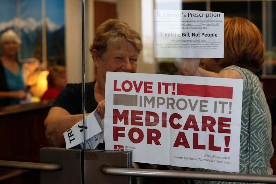A health care activist holds up a sign.