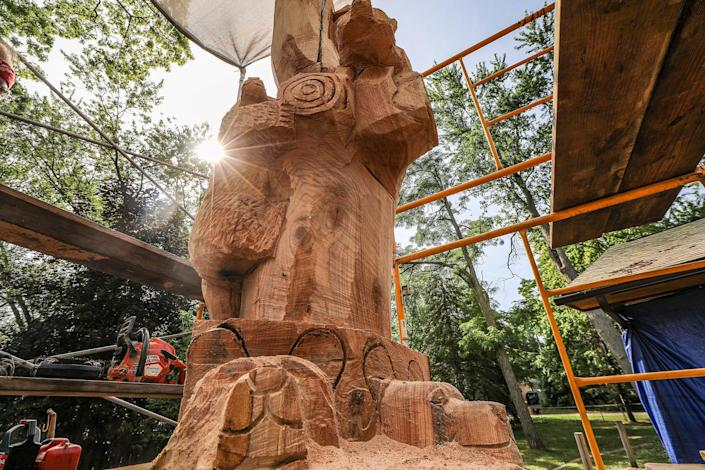 Jim Barnes, of Chainsawcarve.com, transforms Dawn Brusseau's 100-year old tree into a wooden sculpture after pieces of the tree were destroyed by thunderstorms in the backyard of Brusseau's home in Wixom, Michigan, on July 15, 2020.