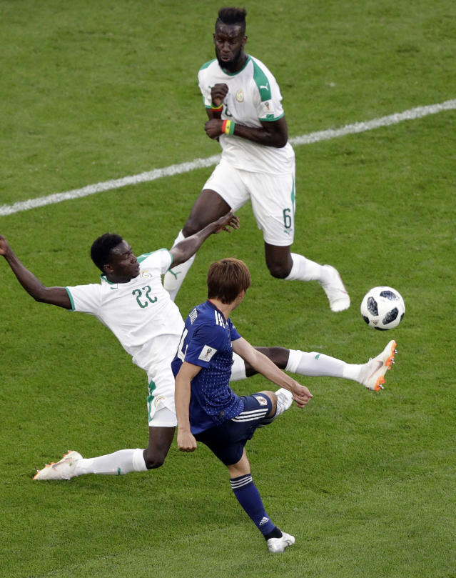 Japan's Takashi Inui, front, shoot to score his site's first goal as Senegal's Moussa Vague, left, fails to defend during the group H match between Japan and Senegal at the 2018 soccer World Cup at the Yekaterinburg Arena in Yekaterinburg , Russia, Sunday, June 24, 2018. (AP Photo/Baker Mark)