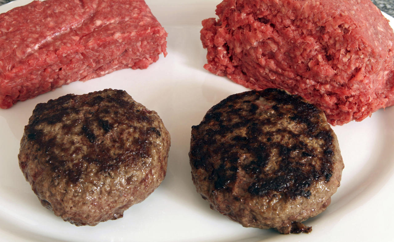"A hamburger made from ground beef containing what is derisively referred to as ""pink slime,"" or what the meat industry calls ""lean, finely textured beef,"" right, and one made from pure 85% lean ground beef are displayed in front of uncooked portions of those meats Thursday, March 15, 2012 in Concord, N.H. Under a change announced Thursday by the U.S. Department of Agriculture, districts that get food through the government's school lunch program will be allowed to say no to ground beef containing the ammonia-treated filler and choose filler-free meat instead. The low-cost filler is made from fatty meat scraps that are heated to remove most of the fat, then treated with ammonium hydroxide gas to kill bacteria such as E. coli and salmonella. (AP Photo/Jim Cole)"