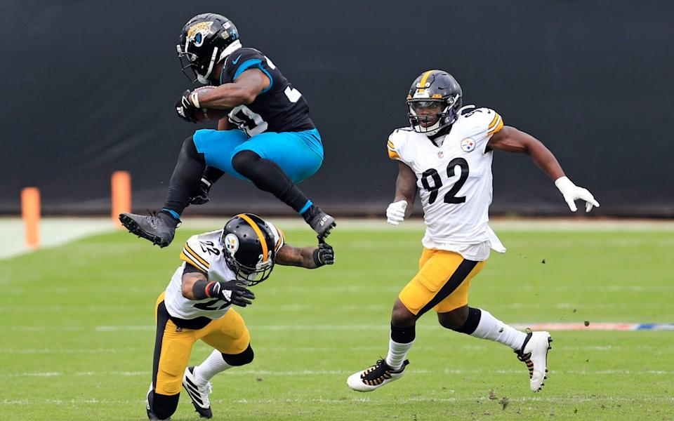 Jacksonville Jaguars running back James Robinson, left, leaps over Pittsburgh Steelers cornerback Steven Nelson (22) as linebacker Olasunkanmi Adeniyi (92) comes in to help during the first half of an NFL football game, Sunday, Nov. 22, 2020, in Jacksonville, Fla.  - AP