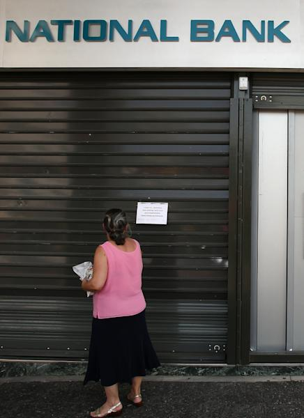 A woman reads an announcement of a strike at a branch of the National Bank of Greece in Athens, Monday, June 30, 2012. Bank workers on Monday held a 24-hour strike to protest cuts under Greece austerity program. (AP Photo/Thanassis Stavrakis)