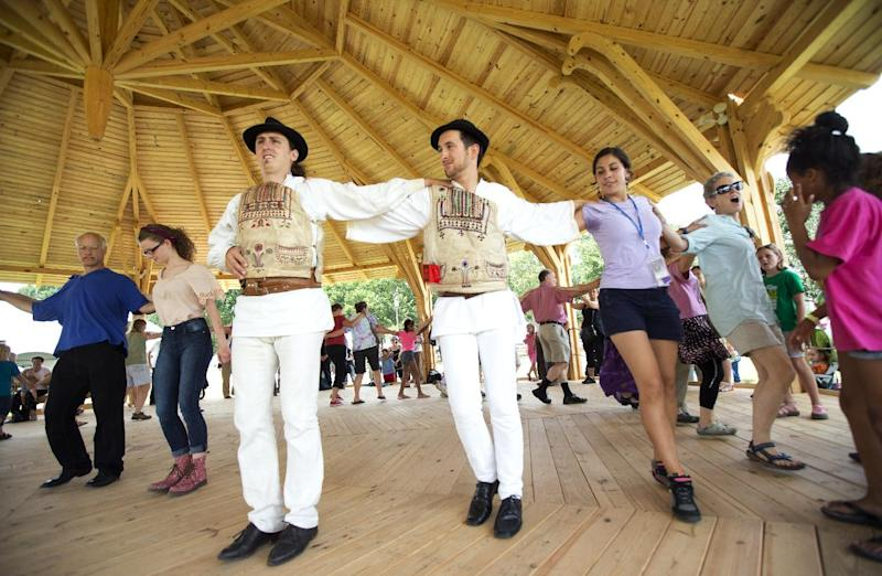 "In this July 3, 2013 photo, Hungarians, from left, Andre Csaba and Lorand Bodor, lead festival visitors in dancing the Hejsza, a Hungarian folk dance, in the Dance Barn, at the 47th annual Smithsonian Folklife Festival on the National Mall in Washington. Hungarian structures are part of the ""Hungarian Roots to Revival"" program in this year's Smithsonian Folklife Festival _ and a personal thrill for the team of carpenters from Hungary who arrived a month prior to the festival to construct the 23-foot Peacock Tower, the Dance Barn and other buildings. (AP Photo/Manuel Balce Ceneta)"
