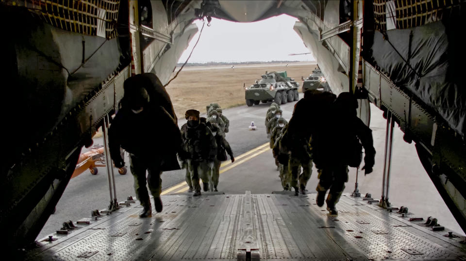 This photo made from the footage provided by Russian Defense Ministry press service on in Tuesday, Nov. 10, 2020 shows Russian peacekeepers taking on a board of military plane in unknown place in Russia. Scores of Russian peacekeepers were heading to Nagorno-Karabakh on Tuesday morning, hours after Armenia and Azerbaijan agreed to halt the fighting over the separatist region in a pact signed with Moscow which envisions the deployment of nearly 2,000 Russian peacekeepers and territorial concessions. (Russian Defense Ministry Press Service via AP)