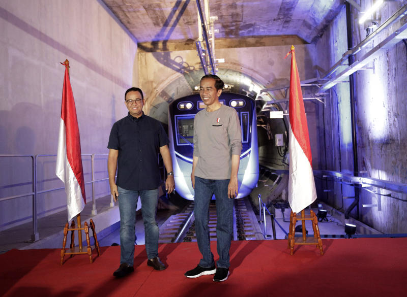 "Indonesian President Joko ""Jokowi"" Widodo, right, stands on a stage with Jakarta Governor Anies Baswedan with the background of a Jakarta Mass Rapid Transit train during the inauguration ceremony of the subway line system in Jakarta, Indonesia, Sunday, March 24, 2019. The 16-kilometer (10-mile) system running south from Jakarta's downtown is the first phase of a development that if fully realized will plant a cross-shaped network of stations on the teeming city of 30 million people. (AP Photo/Dita Alangkara, Pool)"