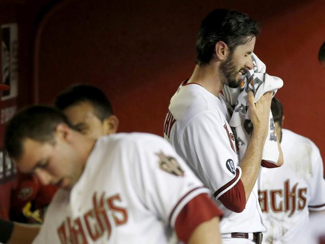 Arizona Diamondbacks' Brandon McCarthy, right, wipes his face after giving up two runs to the Colorado Rockies in the first inning of a baseball game on Friday, Sept. 13, 2013, in Phoenix. (AP Photo/Ross D. Franklin)