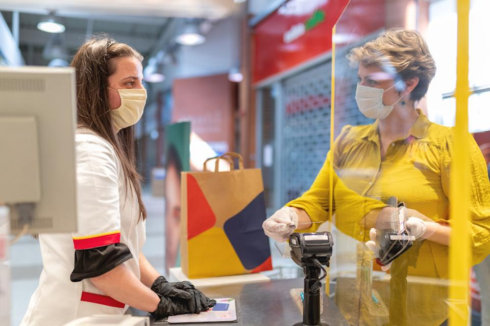 Woman wearing protective face mask and gloves to prevent viruses paying with pay pass credit card on card reader at the cash register and looking at female sales clerk