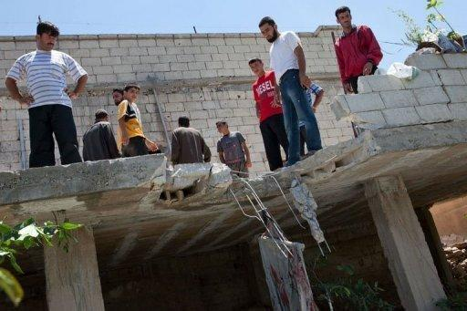 Residents from Kfar Sijna look at the roof of a house, allegedly damaged after a tank shell hit