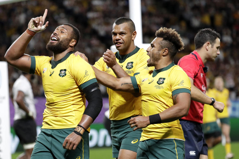 Australia's Samu Kerevi, left, celebrate with teammate Kurtley Beale and Will Genia, right, after scoring a try during the Rugby World Cup Pool D game at Sapporo Dome between Australia and Fiji in Sapporo, Japan, Saturday, Sept. 21, 2019. (AP Photo/Aaron Favila)