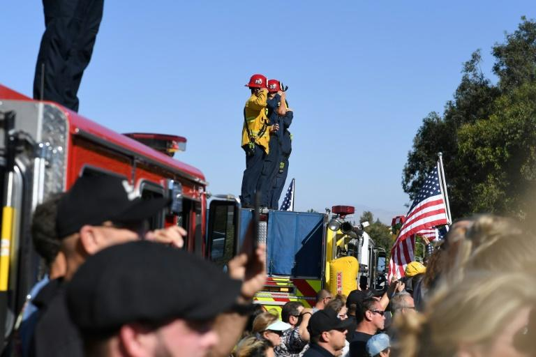 Firefighters salute as a motorcade passes by transporting the body of Sergeant Ron Helus, killed in a shooting at a country bar in Thousand Oaks, California