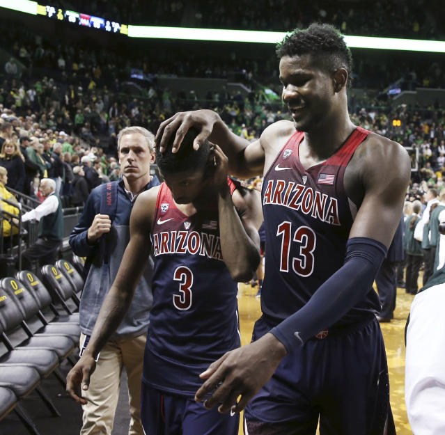 Arizona's Dylan Smith, left, and DeAndre Ayton leave the court after the team's 98-93 overtime loss to Oregon in an NCAA college basketball game Saturday, Feb. 24, 2018, in Eugene, Ore. (AP Photo/Chris Pietsch)