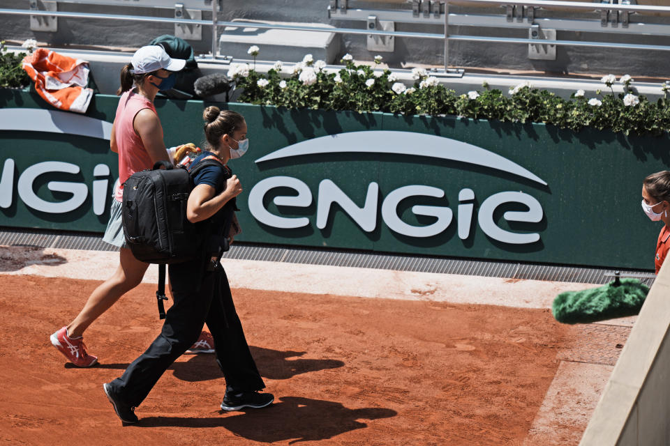 Poland's Iga Swiątek, left, leaves the court with a physiotherapist as she plays Maria Sakkari of Greece during their quarterfinal match of the French Open tennis tournament at the Roland Garros stadium Wednesday, June 9, 2021 in Paris. (AP Photo/Thibault Camus)