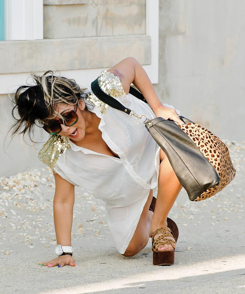 Snooki tumbled to the ground after losing her footing in leopard print wedge sandals on June 21, 2012.