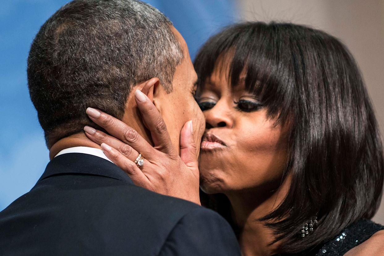 Barack and Michelle Obama kiss at an inauguration reception at the National Building Museum on Jan. 20, 2013, in Washington.